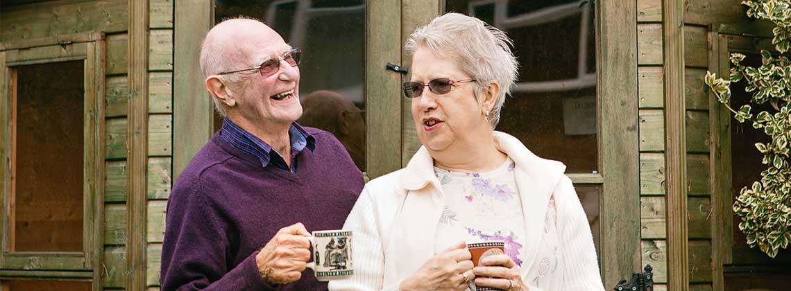 An elderly couple, standing outside drinking tea & conversing, daytime shot.