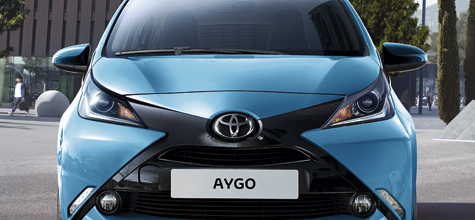 Toyota Aygo, exterior front view, Blue, parked up with other vehicles, daytime city shot with high-rise buildings