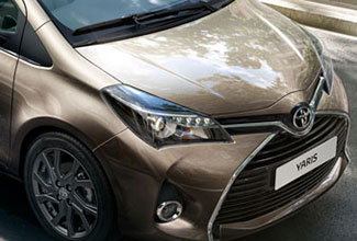 Toyota Yaris, exterior front side view, Bronze, parked in a modern residential with a couple of people walking past