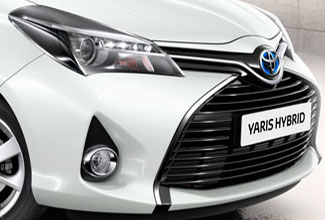 Toyota Yaris, exterior, front side view, White, parked inside a modern & new looking white building